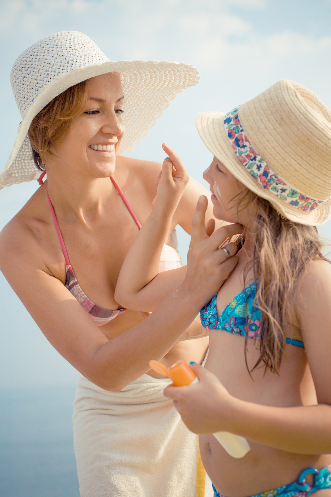 Mother and her daughter applying suntan lotion on the beach